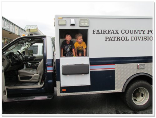 Children enthusiastically explored a police vehicle at the Annandale Shopping Center.